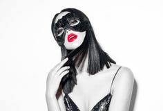 秀丽性感的深色的妇女画象 指向手的女孩佩带的狂欢节黑色羽毛面具,提出产品 库存图片