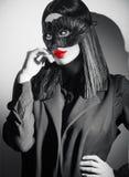 秀丽性感的深色的妇女画象 指向手的女孩佩带的狂欢节黑色羽毛面具,提出产品 免版税图库摄影