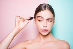 秀丽惯例 女孩举行化妆涂药器 妇女在她的面孔投入了构成 每日构成概念 r 库存图片