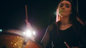 秀丽扭转鼓槌的黑发女孩-打鼓执行,摇滚乐,慢动作 股票视频