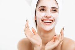 秀丽护肤概念-应用在她的面部皮肤白色的美丽的白种人妇女面孔画象奶油色面具 免版税库存照片