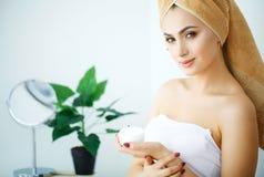 秀丽护肤 应用化妆面霜的美丽的妇女 免版税库存图片