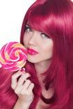 秀丽拿着五颜六色的棒棒糖的女孩画象。魅力构成。 免版税图库摄影