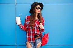 秀丽时尚微笑的妇女画象用在太阳镜的咖啡在蓝色背景 室外 拷贝空间 红色袋子 免版税图库摄影