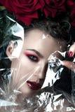 秀丽时装模特儿妇女面孔 与红色玫瑰花的画象 红色嘴唇和钉子 有豪华构成的美丽的深色的妇女, 免版税库存图片