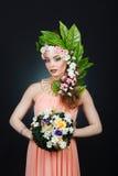 秀丽有花头发的春天女孩 有花的美丽的式样妇女在她的头 发型的本质 夏天 免版税图库摄影