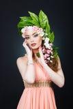 秀丽有花头发的春天女孩 有花的美丽的式样妇女在她的头 发型的本质 夏天 免版税库存照片