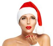 秀丽有送亲吻的圣诞老人帽子的时尚女孩 库存照片
