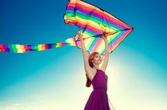 秀丽有飞行的五颜六色的风筝红头发人女孩在蓝天 免版税图库摄影