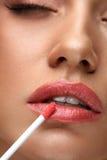 秀丽构成 美丽的妇女申请嘴唇光泽 库存照片