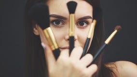 秀丽模型女孩,化妆师藏品将组成刷子和微笑 有完善的美丽的深色的年轻女人 股票录像