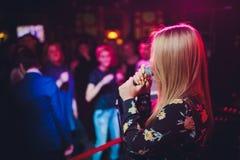 秀丽模型有话筒的女孩歌手唱歌和跳舞在假日发光的背景的 卡拉OK演唱党歌手 免版税图库摄影