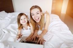 秀丽母亲拥抱有放置在与阳光的白色床的膝上型计算机的小女儿 免版税库存图片