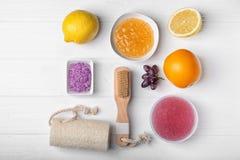 秀丽治疗和身体关心 套身体洗刷和在木背景,平的位置的浴辅助部件 图库摄影
