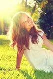 秀丽浪漫十几岁的女孩坐绿草 免版税库存照片