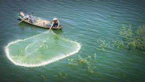秀丽渔夫扔他们的在河的网 免版税库存照片