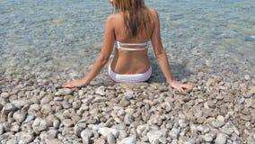 秀丽白色比基尼泳装的被晒黑的妇女坐天蓝色的海的有卵石花纹的岸 股票视频