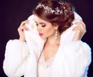 秀丽白色貂皮皮大衣的时装模特儿女孩 婚礼hairst 图库摄影
