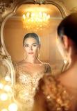 秀丽看在镜子的魅力夫人 免版税库存照片