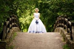 秀丽站立在桥梁的婚礼礼服的新娘 库存图片