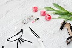 秀丽蓝色聪慧的概念表面方式构成妇女 一部分的一件白色女衬衫、玻璃、唇膏和p 免版税库存图片