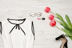 秀丽蓝色聪慧的概念表面方式构成妇女 一部分的白色女衬衫、玻璃、唇膏和桃红色郁金香 顶视图 免版税库存图片