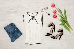 秀丽蓝色聪慧的概念表面方式构成妇女 一部分的白色女衬衫、玻璃、唇膏和桃红色郁金香 顶视图,关闭 库存照片