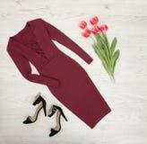秀丽蓝色聪慧的概念表面方式构成妇女 伯根地礼服、黑鞋子和桃红色郁金香 顶视图,轻的木背景 免版税库存图片