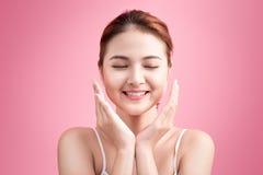 秀丽表面 面部治疗 有干净的完善的皮肤的年轻亚裔妇女接触她的面孔 库存图片