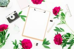 秀丽装饰了概念 博客作者或自由职业者有剪贴板、笔记本、减速火箭的照相机、牡丹和笔的工作区书桌在白色ba 库存图片