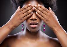 黑秀丽覆盖物眼睛用两只手 库存图片