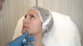 秀丽诊所 在做面孔在女性皮肤的手套的美容师手老化射入 Botox 胶原射入 影视素材