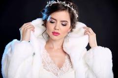 秀丽貂皮皮大衣和白色毛茸的敞篷的时装模特儿女孩 免版税库存照片