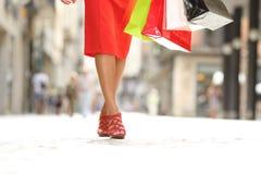 秀丽走妇女的腿拿着购物带来 免版税库存图片