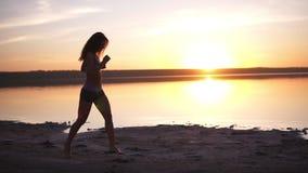 秀丽跑在日落的赛跑者妇女 跑步沿沿海健康生活方式概念的少妇 慢的行动 影视素材