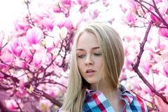 秀丽金发碧眼的女人肉欲的画象有桃红色花的在树从 免版税图库摄影