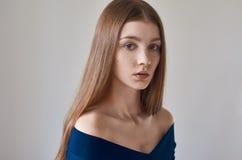 秀丽题材:一个美丽的女孩的画象有雀斑的在她的面孔和穿在白色背景的一件蓝色礼服在studi 免版税库存照片
