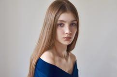 秀丽题材:一个美丽的女孩的画象有雀斑的在她的面孔和穿在白色背景的一件蓝色礼服在studi 免版税库存图片