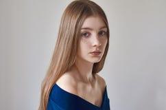 秀丽题材:一个美丽的女孩的画象有雀斑的在她的面孔和穿在白色背景的一件蓝色礼服在studi 库存照片