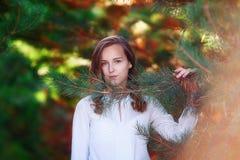 年轻秀丽,俏丽的wooman在云杉附近的明亮的秋天公园 库存照片