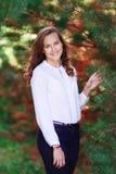 年轻秀丽,逗人喜爱的微笑的wooman在云杉附近的秋天公园 免版税库存图片