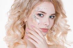 秀丽年轻卷曲白肤金发的妇女妇女画象有淡色修指甲的和完善的艺术化妆与闪烁 查出 免版税库存照片