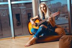 秀丽年轻白肤金发的夫人弹吉他 免版税库存照片