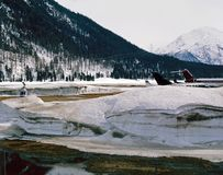 私人喷气式飞机、飞机和一架直升机在瑞士的积雪的风景 免版税库存图片