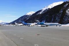 私人喷气式飞机、飞机和一架直升机在瑞士的积雪的风景 免版税库存照片