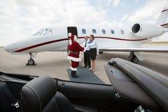 私人喷气式飞机乘员组招呼圣诞老人 免版税库存照片