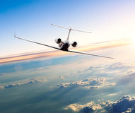私人喷气式飞机在云彩上的飞机飞行 免版税库存图片