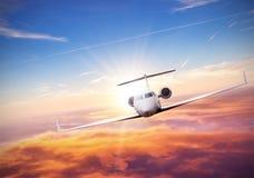 私人喷气式飞机在云彩上的飞机飞行 库存照片