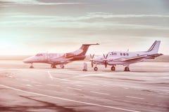 私人喷气式飞机在机场飞行停车处 在日落的私有飞机, 图库摄影