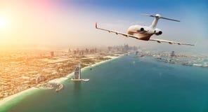 私人喷气式飞机在迪拜市上的飞机飞行美丽的日落锂的 免版税图库摄影